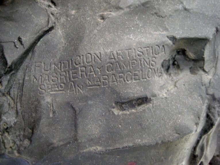 Detall de la marca del fonedor Masriera i Campins a l'espatlla esquerra de la figura