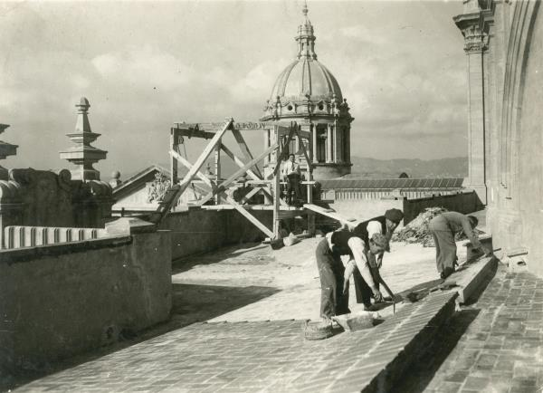 Construction workers working on the roof of the Palau Nacional.