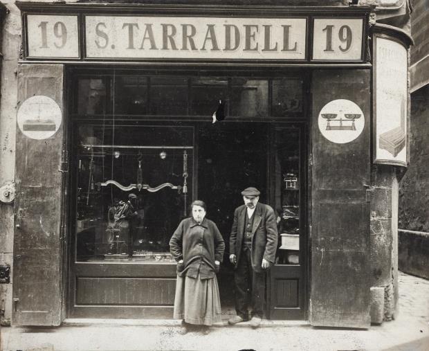 Serafí Tarradell i la seva muller davant l'establiment de la seva propietat al núm. 19 de la plaça de la Llana. Barcelona, principis del segle xx. Donació de Núria i Eulàlia Tarradell i Font.