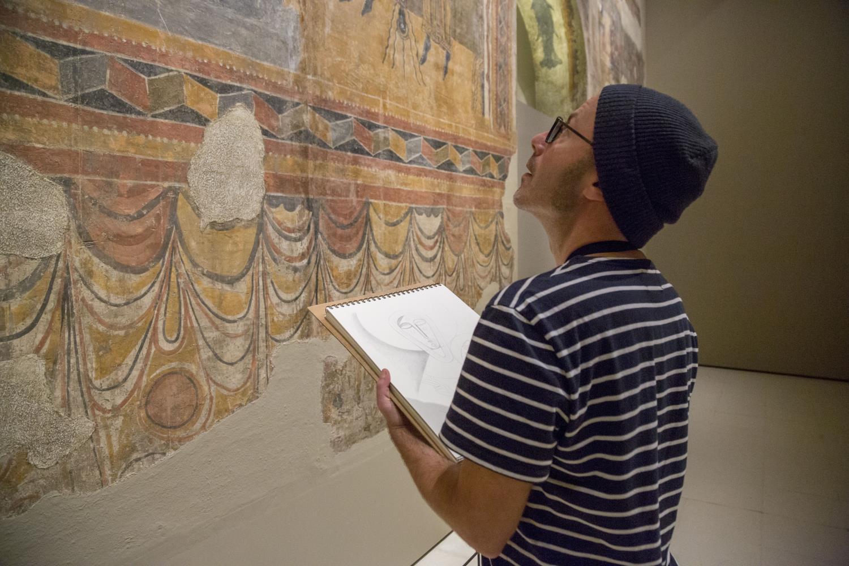 El artista Iker Spozio Ante una de las pinturas murales románicas de la colección del museo